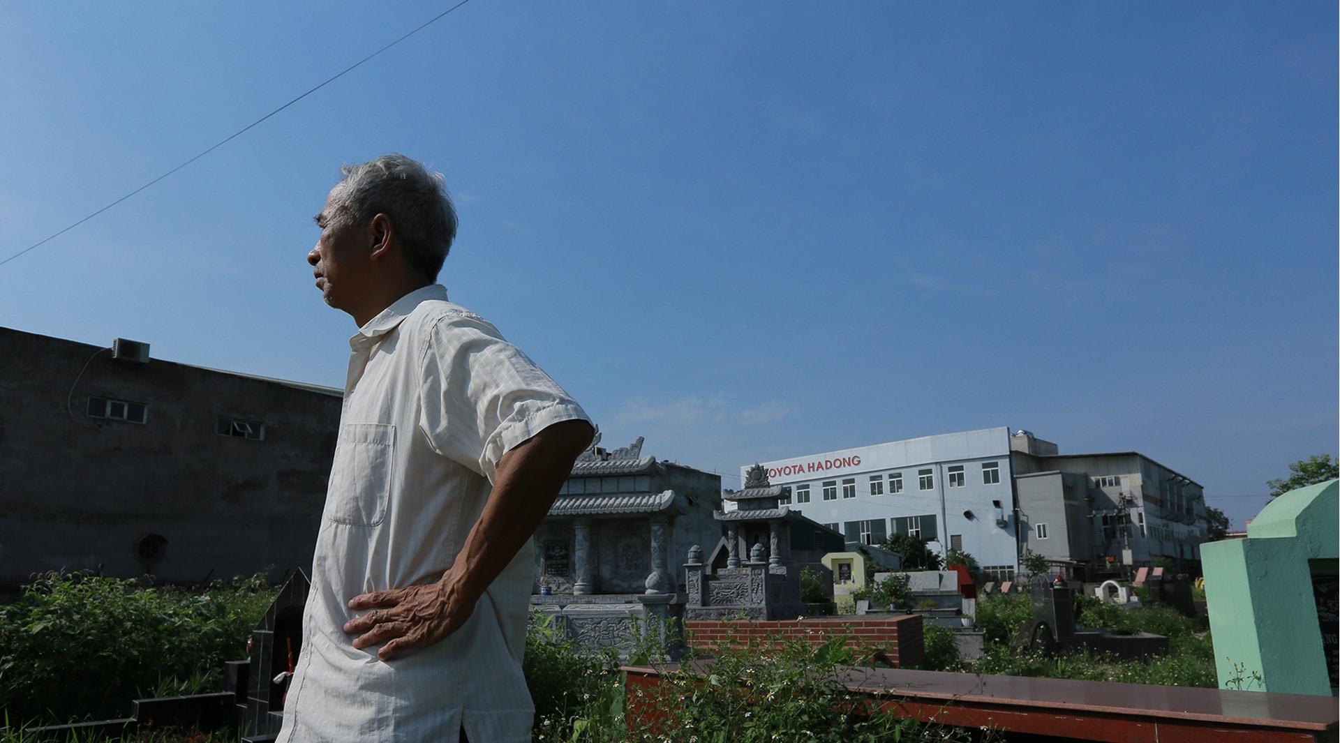 Ông Mô đứng cạnh nghĩa trang cũ và mảnh đất đã bị thu hồi